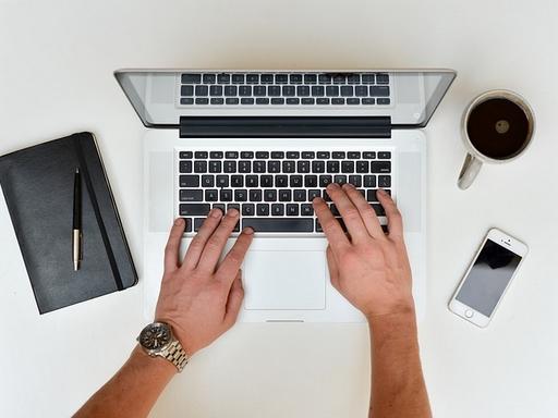 kezek egy laptop fölött