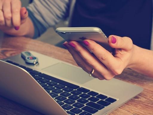 nő kezében telefon, előtte laptop