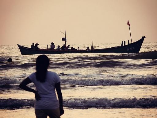 menekültek a tengeren egy csónakban, parton álló nő figyeli