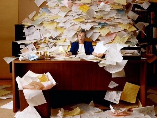 irodai dolgozót borítanak el a papírok