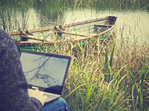 folyóparton, egy csónak mellett laptopon dolgozó férfi
