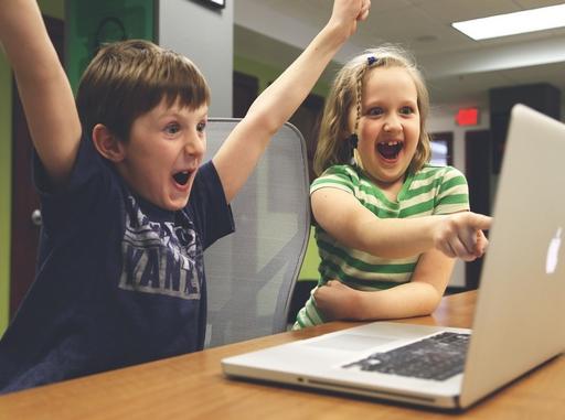 gyerekek egy számítógép előtt nagyon örülnek