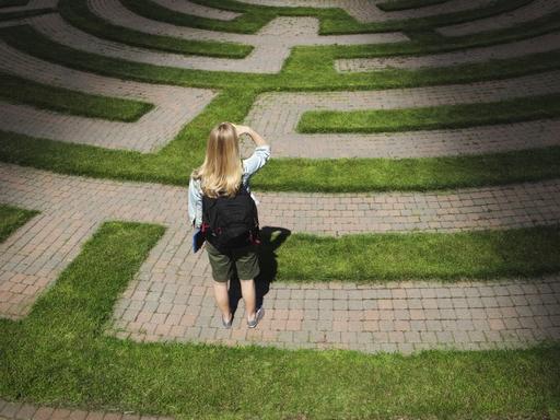 egy nő áll egy labirintus bejáratánál
