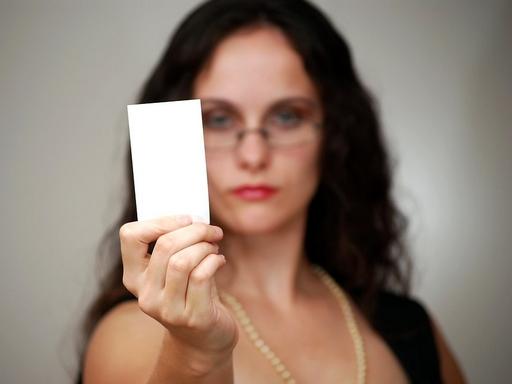 nő névjegyet emel fel