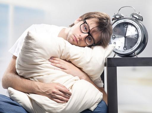 álmos ember egy nagy órával és párnával