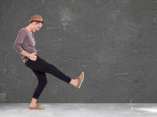 relaxed casual young man kicking and smiling