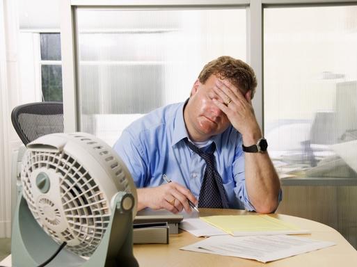 hőségben szenvedő ember az irodában