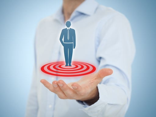 Target customer (marketing) concept. Businessman hold target customer represented by virtual icon of man standing on target. Central composition.