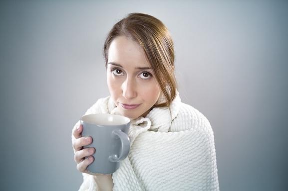 nő takaróban, teával a kezében