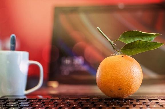 egy narancs és teásbögre billentyűzeteten