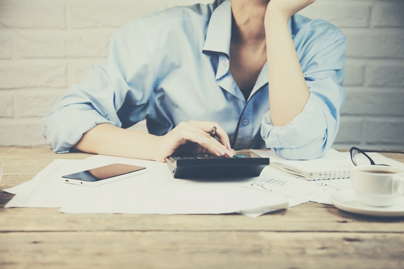 Close up of female accountant making calculations. Savings, finances and economy concept