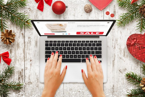 Christmas sale on laptop. Woman shopping on market website. Top view of wooden table with christmas new year decorations, tree and gift.