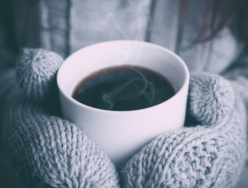 kávésbögrét fogó kéz hidegben