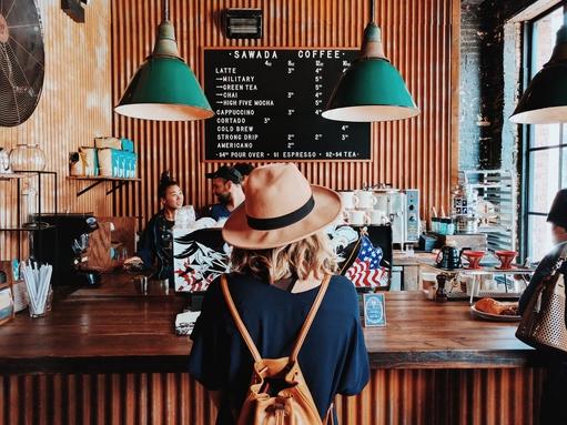 nő áll egy kávézó pultjánál