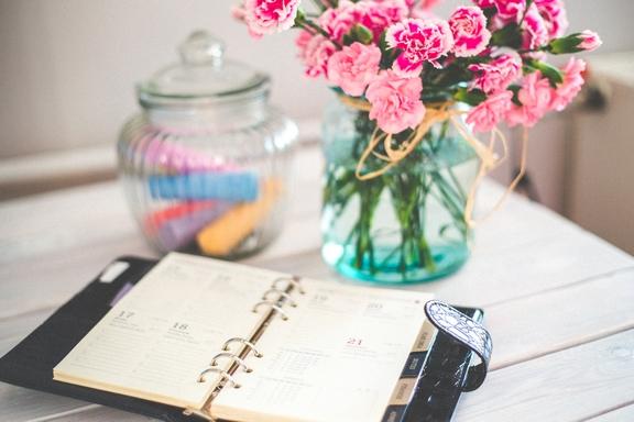 határidőnapló asztalon, virággal
