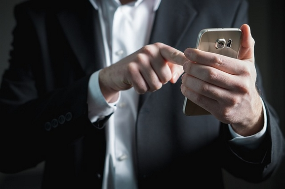 okostelefonon chatelő férfi
