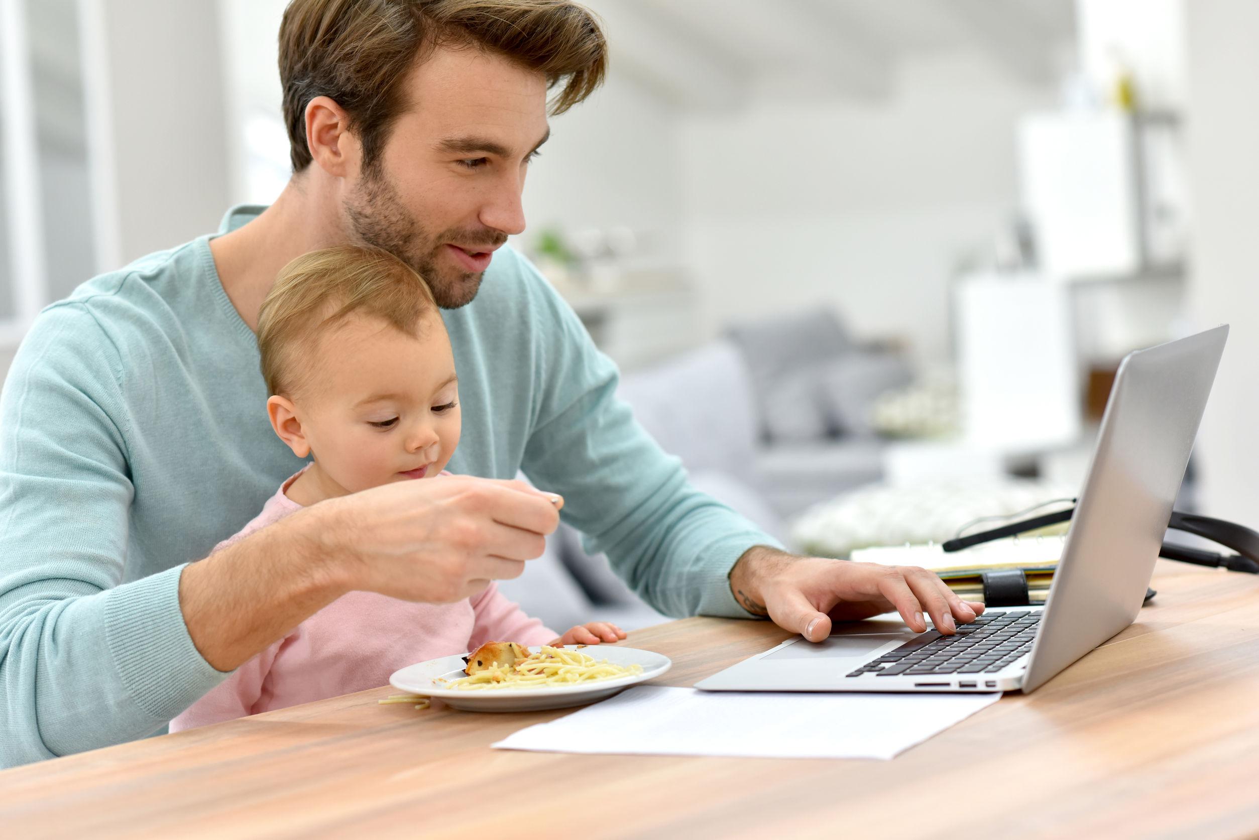 otthonról dolgozó apa gyerekkel az ölében
