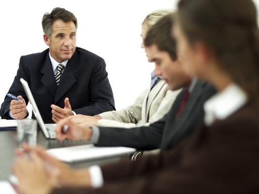 főnök és alkalmazottak egy asztal körül